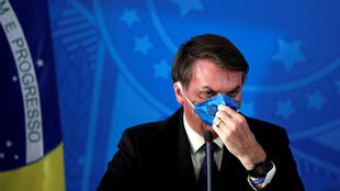 Brazil's President Jair Bolsonaro adjusts his protective face mask at a press statement during the coronavirus disease (COVID-19) outbreak in Brasilia, Brazil, March 20, 2020. Picture taken March 20, 2020.