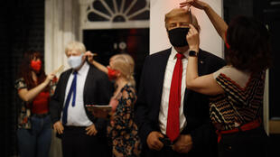 Artists at London's Madame Tussauds check the masks on the wax figures of British PM Boris Johnson and US President Donald Trump