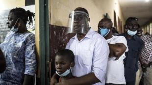 Electores guineanos hacen fila en un centro de votación de la capital Conakri, en Guinea, el 18 de octubre de 2020.