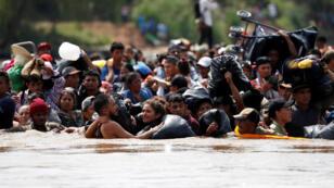 Migrantes centroamericanos caminan por el río Suchiate, la frontera natural entre Guatemala y México, en su intento de llegar a Estados Unidos desde Tecun Uman, Guatemala, el 29 de octubre de 2018.