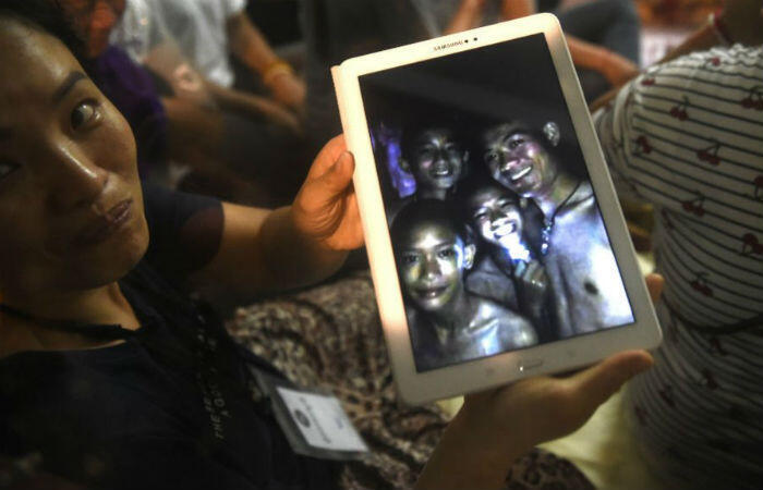 Lillian Suwanrumpha, AFP | A happy family member shows a picture of the missing boys taken by rescue divers in a Thailand cave.