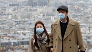 سياح يرتدون كمامات واقية على تلة مونمارتر بباريس، 16 مارس/آذار 2020.