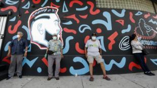 Personas guardan la distancia social mientras asisten a un evento de distribución de mascarillas en Miami, Estados Unidos el 26 de junio de 2020.