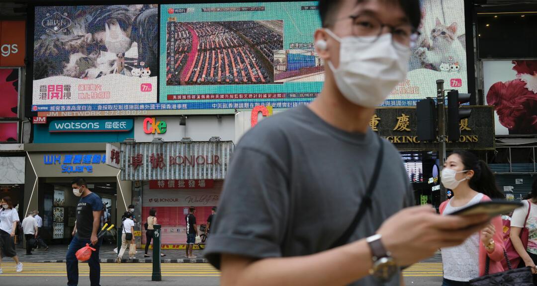 Gente pasando frente a una pantalla de televisión que muestra noticias sobre la aprobación de la ley de seguridad de Hong Kong, el 28 de mayo de 2020.
