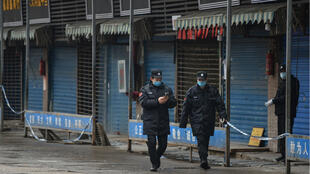 Security guards patrol outside the Huanan Seafood Wholesale Market where the coronavirus was detected.