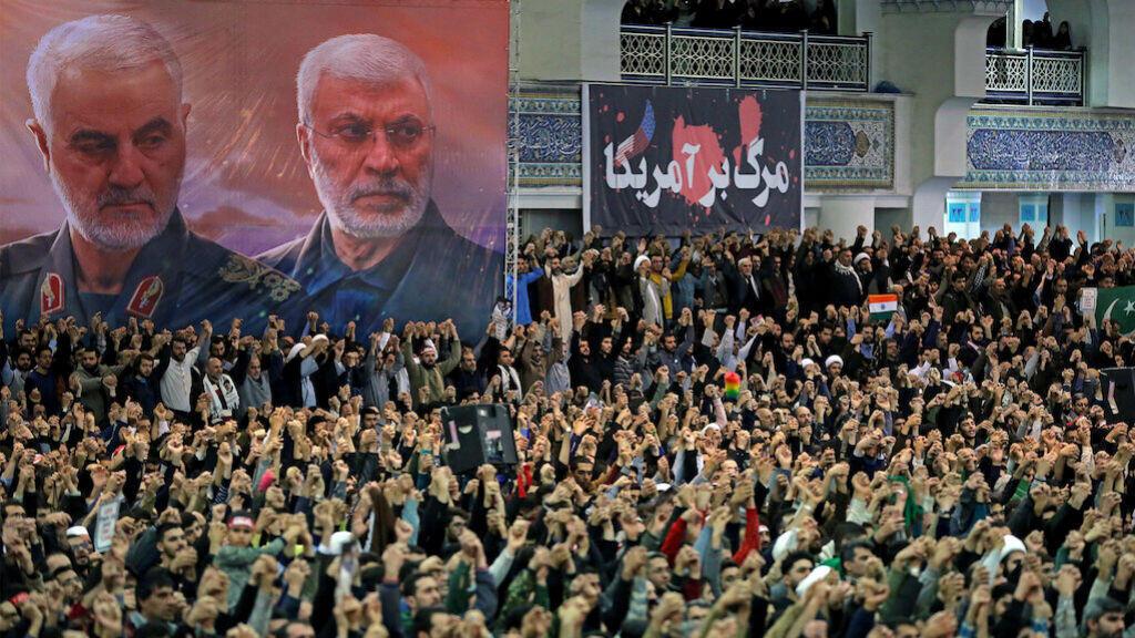 Un cartel muestra al difunto comandante militar iraní Qassem Soleimani y al difunto comandante de la milicia iraquí Abu Mahdi al-Muhandis, mientras los fieles iraníes cantan consignas durante el sermón de las oraciones del viernes dirigido por el líder supremo de Irán, el ayatolá Ali Khamenei, en Teherán, Irán, el 17 de enero de 2020.
