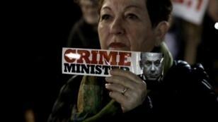 إحدى المشاركات في مظاهرة معارضة لرئيس الوزارء الإسرائيلي بنيامين نتانياهو.