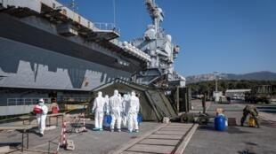 Opération de désinfection autour du porte-avions Charles de Gaulle le 12 avril 2020, après son arrivée à Toulon, en France.