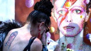 Une fan se recueille devant le portrait de David Bowie dans le quartier de Brixton, à Londres, le 11 janvier 2015.