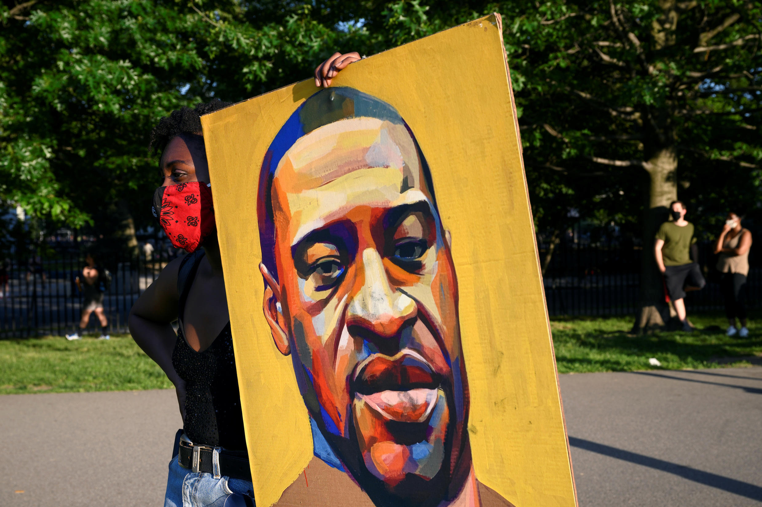 A demonstrator holds a painting depicting George Floyd during a protest against racism and police violence in New York on June 9, 2020.