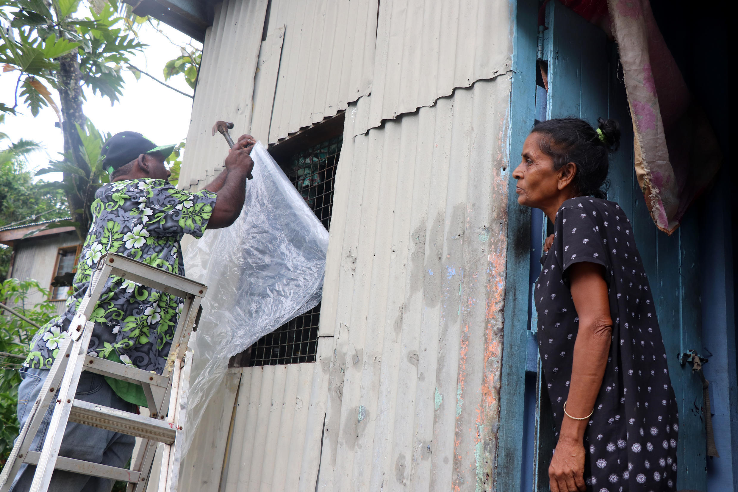 A resident secures his house by placing plastic sheets on the windows ahead of the arrival of super Cyclone Yasa in Fiji's capital city of Suva