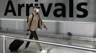 مسافر يضع كمامة أثناء وصوله إلى مطار هيثرو في شرق لندن في 22 أيار/مايو 2020
