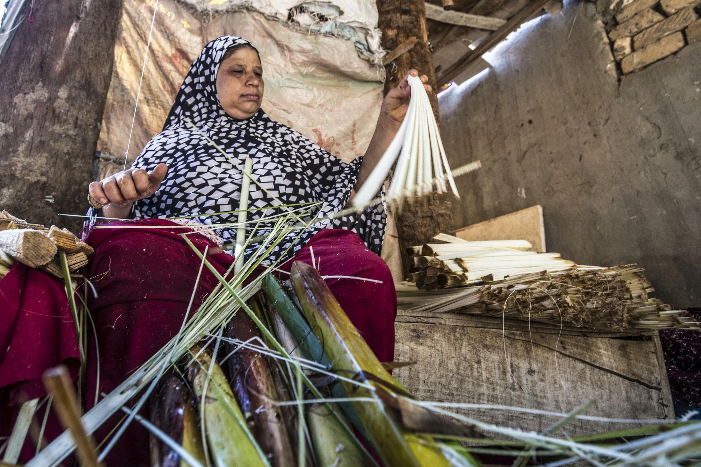 امرأة تقطع بردية إلى شرائح رقيقة في ورشة بالكراموس