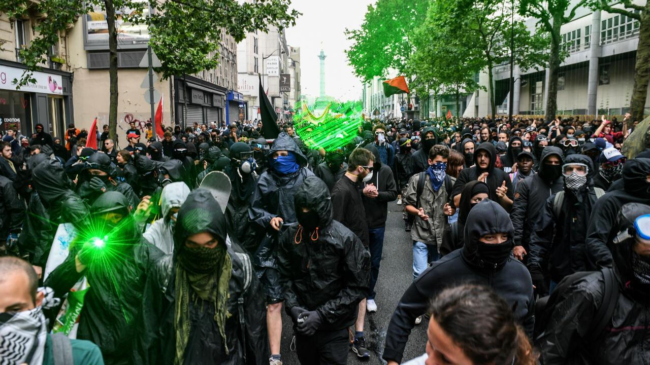 """Des manifestants connus comme """"black blocks"""" défilent à Paris, le 22 mai 2018, contre les politiques du président Emmanuel Macron."""