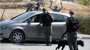 Des policiers israéliens contrôlent un conducteur palestinien à la sortie du quartier de Jabal Mukaber, à Jérusalem-Est, le 14 octobre 2015.