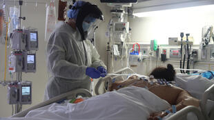 A medical staff member treats a patient suffering from Covid-19 in the intensive care unit at Scripps Mercy Hospital in Chula Vista, California, on May 12, 2020.