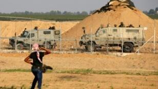 محتج فلسطيني يلقي بالحجارة على جنود إسرائيليين خلال تظاهرة على الحدود بين إسرائيل وغزة في 9 تشرين الثاني/نوفمبر 2018