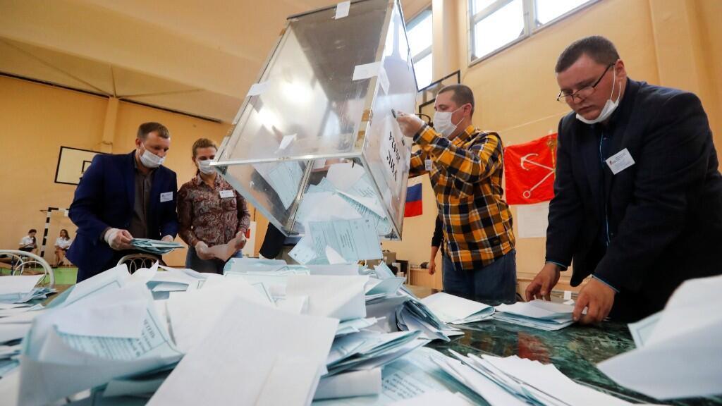 Varias personas voltean una urna llena de votos para iniciar su recuento. En San Petersburgo, Rusia, el 1 de julio de 2020.