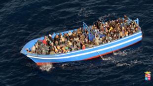 Des migrants clandestins sur une embarcation de fortune près des côtes italiennes.