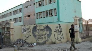 Un partisan du général Haftar à Benghazi le 17 juillet 2017 devant un graffiti représentant l'ancien dictateur libyen Mouammar Kadhafi.
