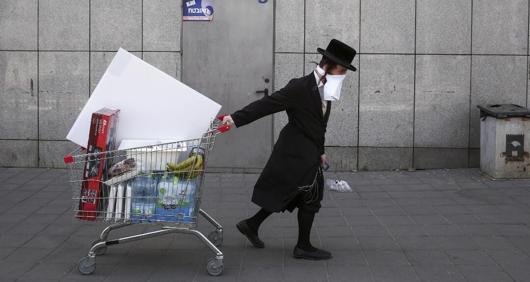 Un judío ultraortodoxo usa una máscara protectora improvisada mientras jala un carrito. Tel Aviv, Israel, el 3 de junio de 2020.