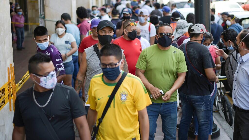 Un grupo de personas transita por una calle, luego de que las autoridades permitieran que algunas empresas reabrieran el miércoles después de una caída en las muertes diarias por el brote del Covid-19. En Guayaquil, Ecuador, el 20 de mayo de 2020.