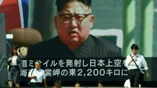 مشاة يعبرون في طوكيو أمام شاشة عملاقة تبث تقريرا إخباريا ظهرت خلاله صورة زعيم كوريا الشمالية كيم جونغ-أون في 15 أيلول/سبتمبر 2017.