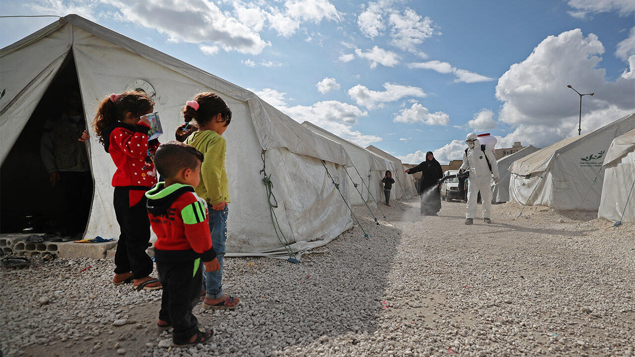 Displaced Syrian children watch as a sanitation worker disinfects their camp next to the Idlib municipal stadium in the northwestern Syrian city on April 9, 2020, during a campaign to limit the spread of the coronavirus (COVID-19) pandemic.