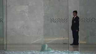 A security guard looks at shattered glass at a shopping mall in Mexico City on July 25, 2019 where two Israelis suspected of mafia links were shot dead in a restaurant.