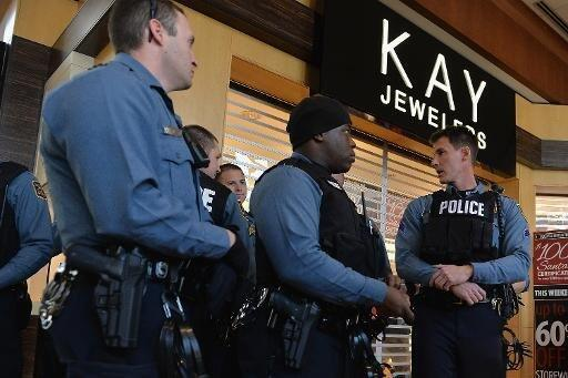 Missouri police officers watch as protesters demonstrate in Brentwood, Missouri, in November 2014.