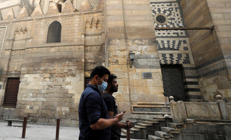 مصريان يتجولان في شارع المعز في الحسين والأزهر مع إغلاق المساجد في القاهرة القديمة، حيث تكثف مصر جهودها لإبطاء تفشي فيروس كورونا، القاهرة، مصر، 6 أبريل/ نيسان 2020.
