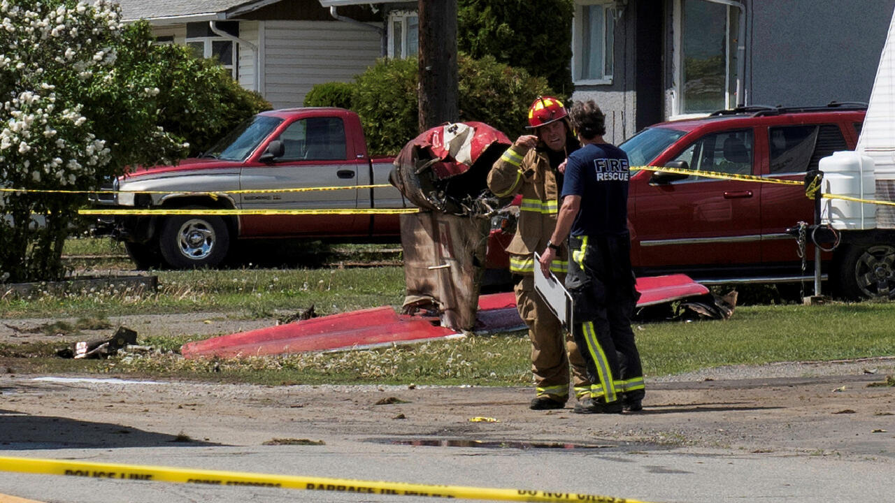 Fire officials talk in a residential neighbourhood street in front of the tail wreckage from a Royal Canadian Air Force Snowbirds jet after a member of the exhibition team crashed shortly after takeoff in Kamloops, British Columbia, Canada, May 17, 2020.