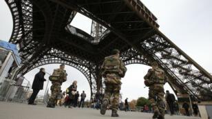 جنود فرنسيون يقومون بدوريات حراسة قرب منطقة المشجعين أمام برج إيفل