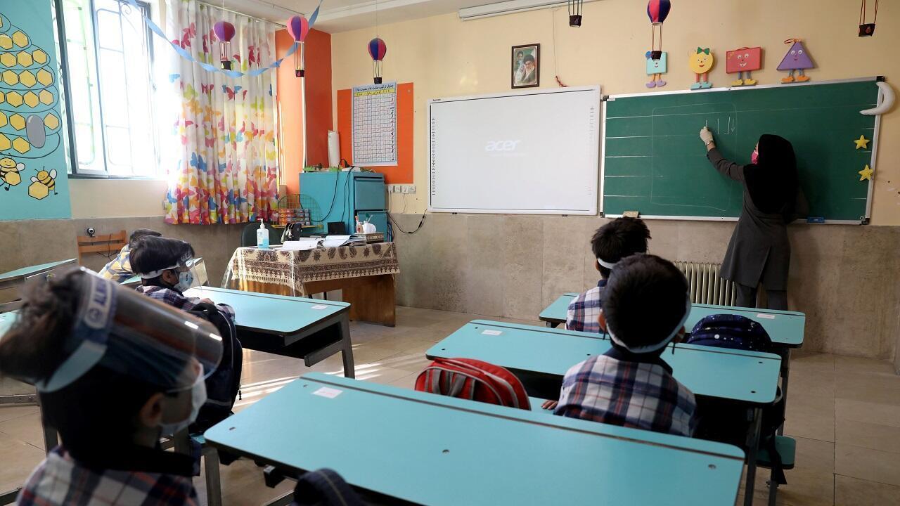 الأطفال والمعلمة يرتدون أقنعة واقية مخافة تفشي فيروس كورونا، مدرسة المهدي في طهران. إيران في 5 سبتمبر/أيلول 2020.