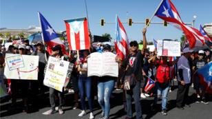 La gente canta consignas mientras agita banderas puertorriqueñas, durante las protestas en curso que piden la renuncia del gobernador Ricardo Rosselló, en San Juan, Puerto Rico, el 22 de julio de 2019.