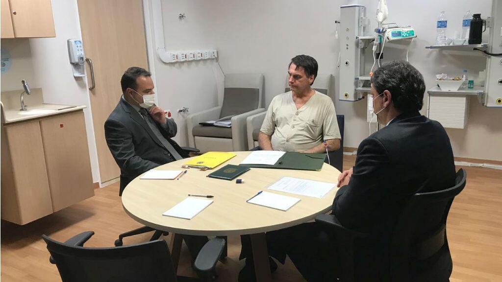 El presidente de Brasil, Jair Bolsonaro, conversa con el ministro de Infraestructura, Tarcisio Gomes de Freitas, y con el jefe adjunto de Asuntos Legales de la Casa Civil de la Presidencia de la República, Jorge Oliveira en el Hospital Albert Einstein en Sao Paulo, Bras