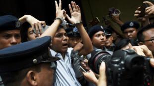 الصحفي البورمي وا لون (وسط) اثناء مرافقة الشرطة له بعدما الحكم بسجنه في رانغون بتاريخ 3 أيلول/سبتمبر 2018