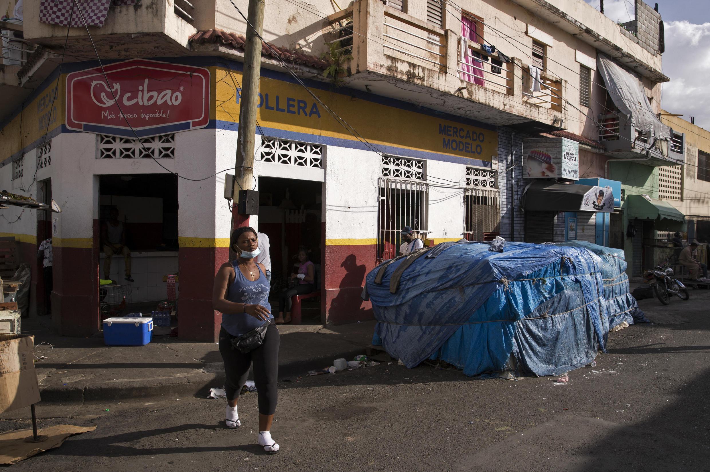 """Imagen de archivo. Una mujer cruza una calle en un sector llamado """"Pequeño Haití"""" en Santo Domingo, el 1 de marzo de 2021. El presidente dominicano, Luis Abinader, anunció la construcción de un muro en la frontera con Haití para reducir la migración ilegal."""