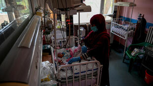 A nurse takes care of newborn babies rescued and brought to the Ataturk Children Hospital after their mothers were killed in an attack on a Kabul maternity hospital