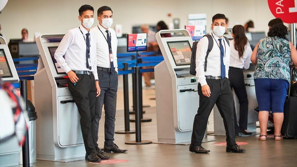 Personal de los terminales del Aeropuerto Internacional Jorge Chavéz utilizan tapabocas como medida de protección el miércoles en Lima.