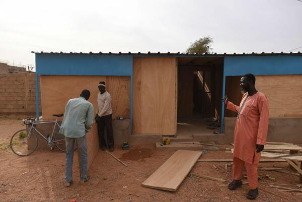 Ousmane Maidambe (à droite), le directeur régional des migrations et des réfugiés, devant l'annexe en train d'être construite pour fluidifier les entretiens de demandes d'asile.