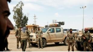 قوات سوريا الديمقراطية وجنود أمريكيون (يسار) قرب البوكمال، 1 أيار/مايو 2018.