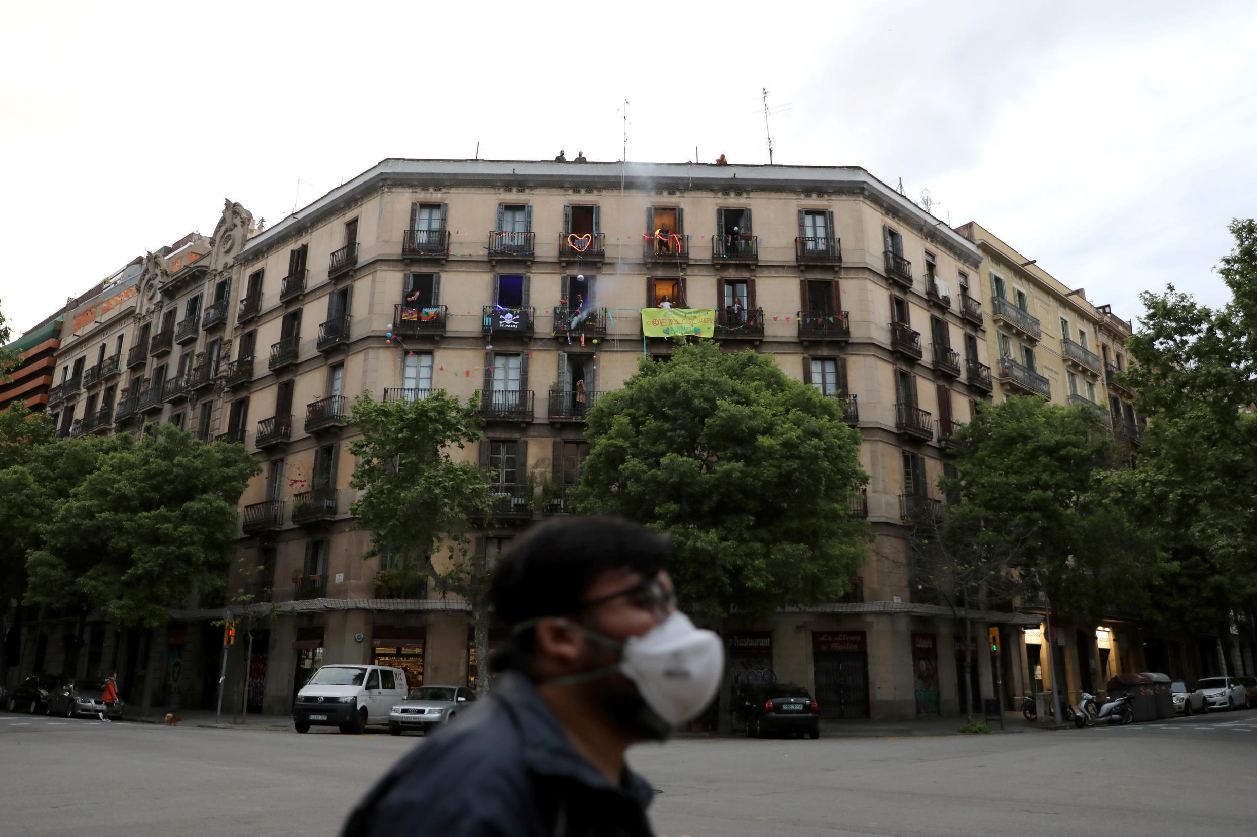 A man wearing a face mask walks in front of a building where neighbours confined in their homes dance on their balconies, amid the spread of the coronavirus disease (COVID-19), in Barcelona, Spain April 17, 2020.