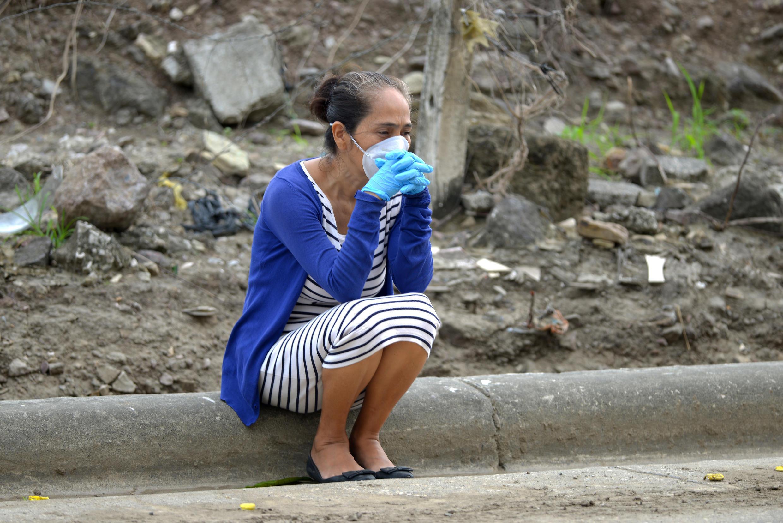 Una mujer con una máscara y guantes espera a las afueras de un cementerio de Guayaquil, la ciudad más poblada de Ecuador, el 1 de abril de 2020