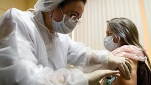 Una enfermera con tapabocas procede a una vacunación contra la enfermedad del nuevo coronavirus con la vacuna Sputnik V (Gam-COVID-Vac) en una clínica de Moscú, Rusia, el 5 de diciembre de 2020.