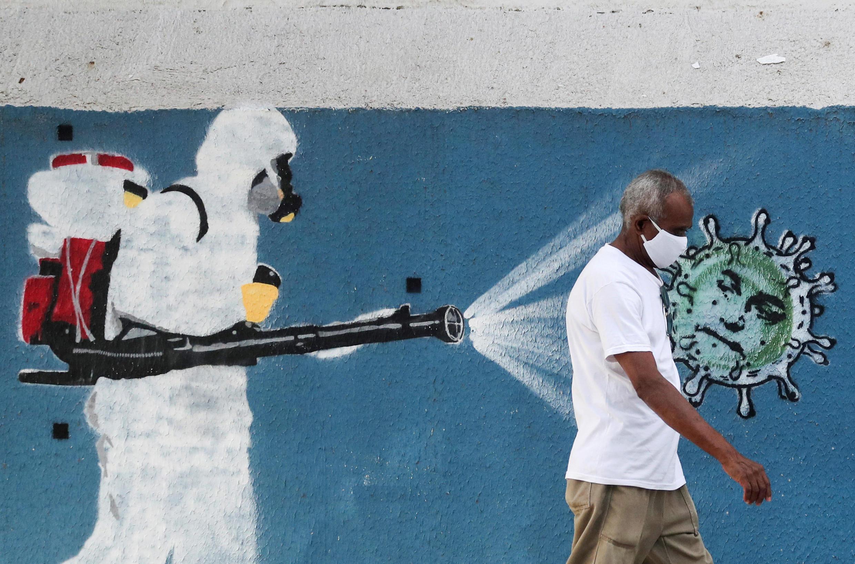 Sur ce graffiti, à Rio de Janeiro, un homme en tenue de protection pulvérise du virus sur le visage du président brésilien Jair Bolsonaro.