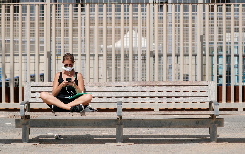 Une femme assise sur un bac, près de la plage de Barceloneta, le 9 juillet 2020.