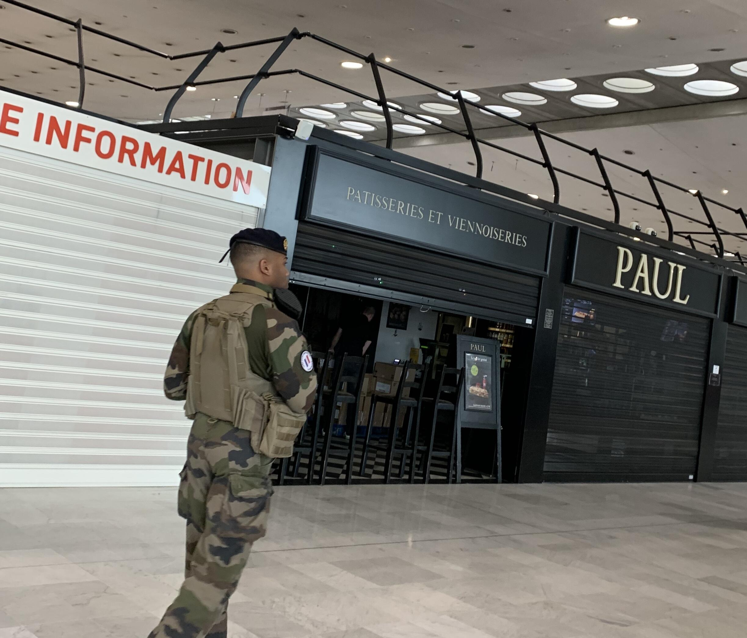 A military patrol in Charles DeGaulle airport passes in front of closed concessions on March 16, 2020.