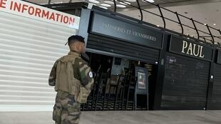 A military patrol in Charles de Gaulle airport passes in front of closed concessions on March 16, 2020.