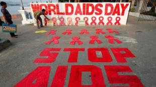 Un hombre coloca un cartel mientras prepara un mensaje durante una campaña de concientización sobre el VIH / SIDA en la víspera del Día Mundial del SIDA en Calcuta, India, el 30 de noviembre de 2017.